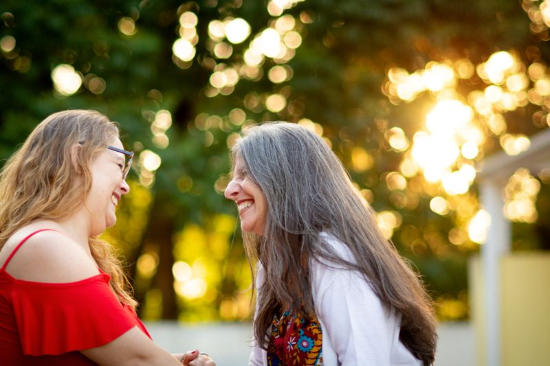Shot of two women, looking at each other and smiling