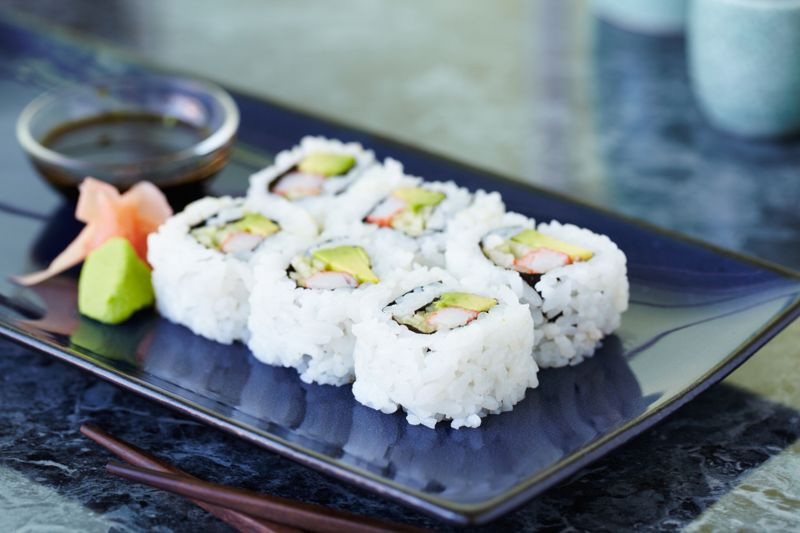 California roll on blue rectangular plate with wasabi, ginger and soy sauce. Shot with shallow focus on front sushi.