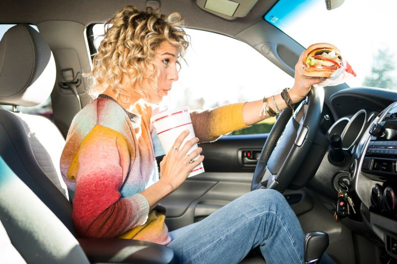 Eating burgers from a fast food chain while driving a car.
