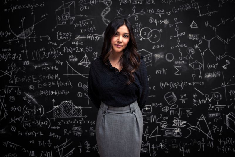 A young woman stands serious in front of a chalkboard filled with mathematical equations, showing individuality, intelligence and creativity