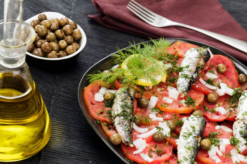 Fish salad with tomatoes sardines olives onions and dill