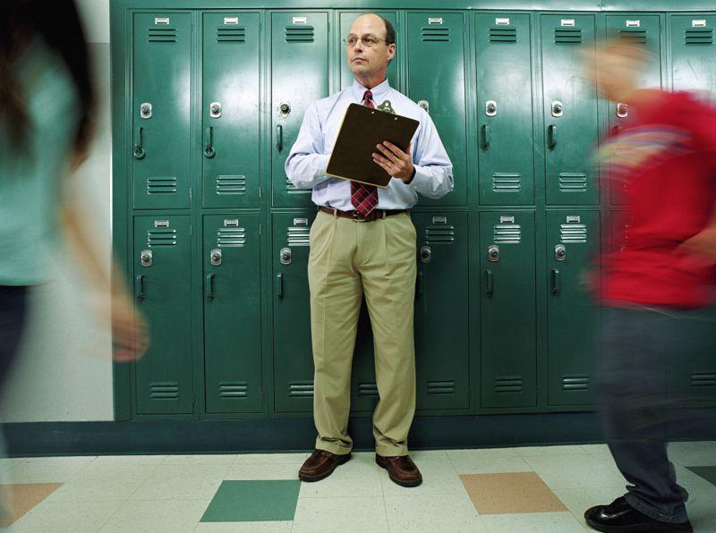Man in school hallway with clipboard