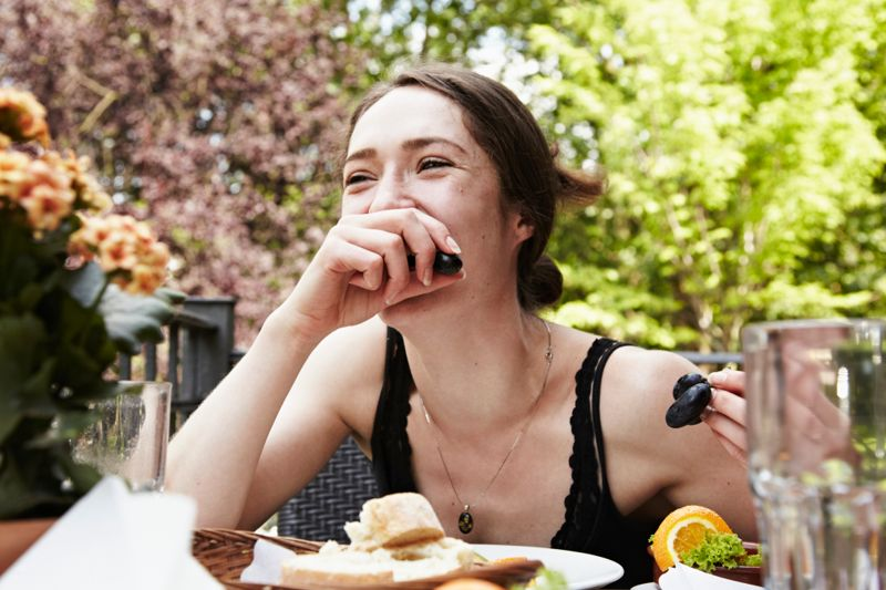 portrait of a young woman fooling around at table eating grapes