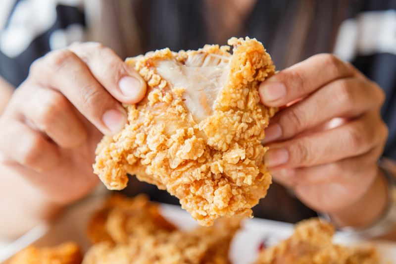 Hand holding Fried chicken and eating in the restaurant