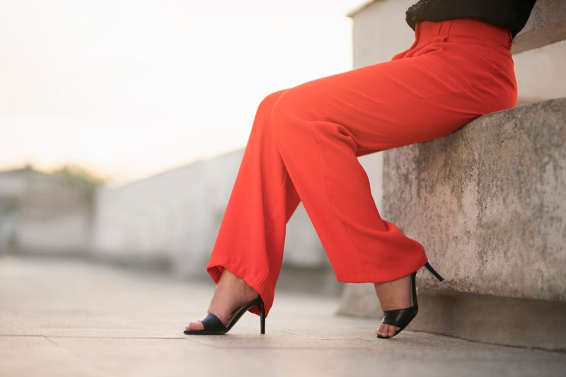 Fashion portrait of an unrecognizable young woman sitting at the balcony in red trousers and high heels; cut out.
