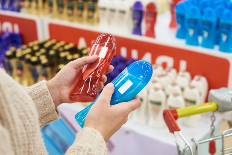 Woman buyer chooses a shampoo in the store