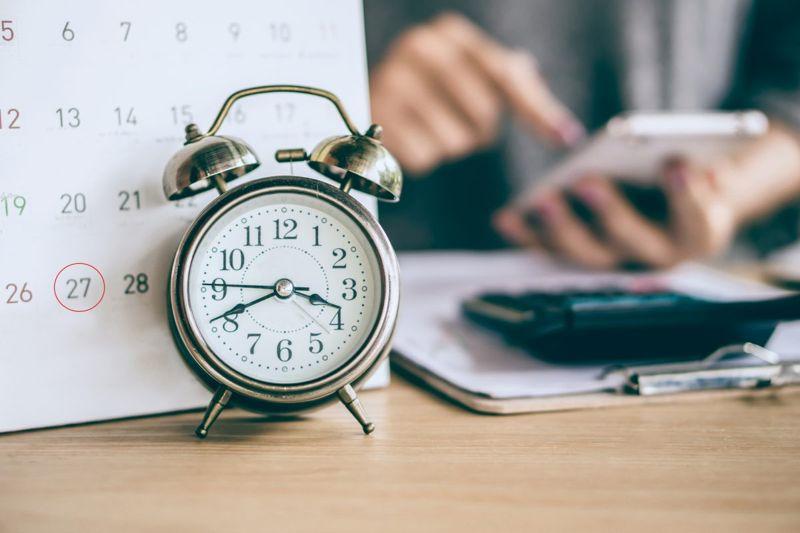 Calendar and alarm clock on table.