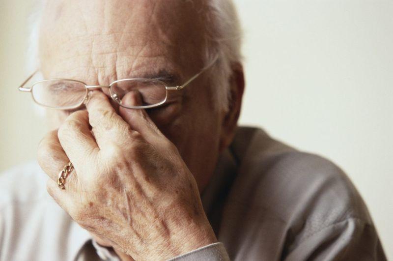 man rubbing eyes aura