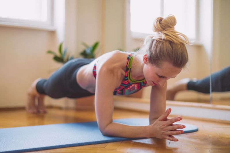 woman in forearm plank engaging abdominals