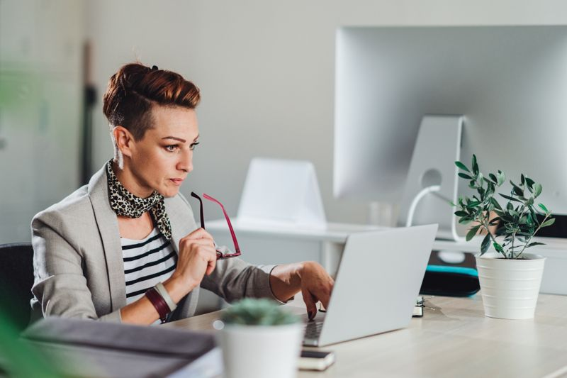 Business woman wearing grey suit sitting at the desk and using laptop in the office