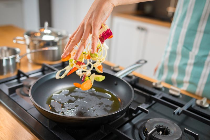 Close-up of chef's hand adding chopped vegetables to pan in kitchen.