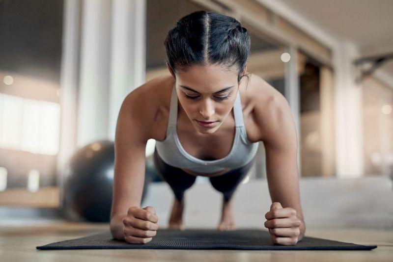 woman in forearm plank elbows below shoulders