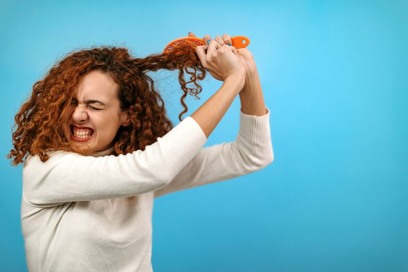 Woman standing in front of blue background combing her hair
