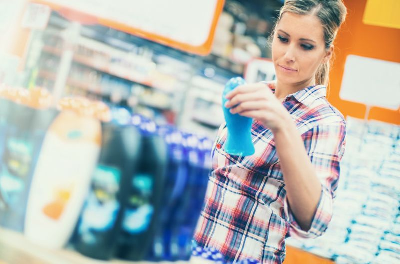 Closeup of late 20's attractive blond woman buying some cosmetics in local supermarket. She's reaching for a certain product placed on wooden shelf.The woman is wearing blue jeans and casual shirt with yellow t-shirt underneath. Low angle shot, side view. Toned image. Tilt shot.