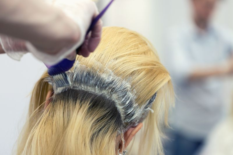 A blonde female bleaching hair in studio