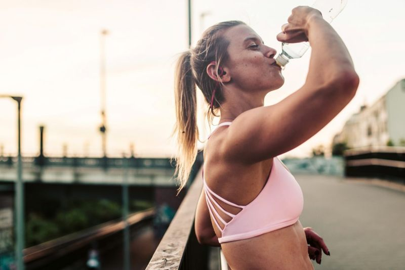 Woman drinking from bottle after workout.