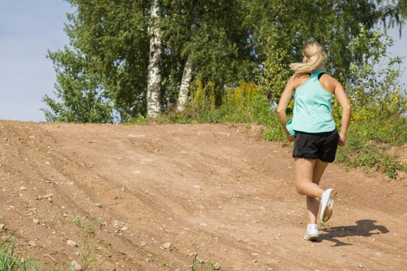 Young woman running up hill.
