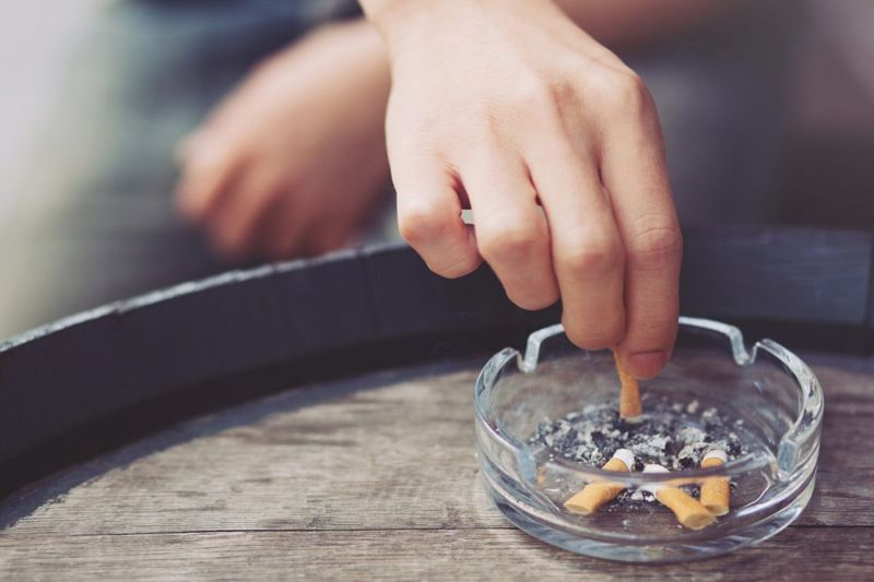Hand putting out cigarette in ashtray.