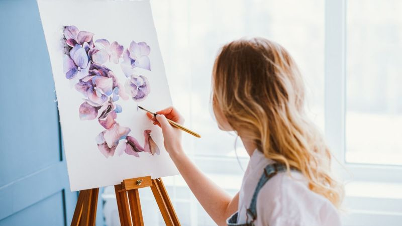 Woman painting on canvas.