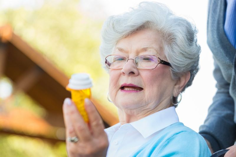 woman reading prescription bottle