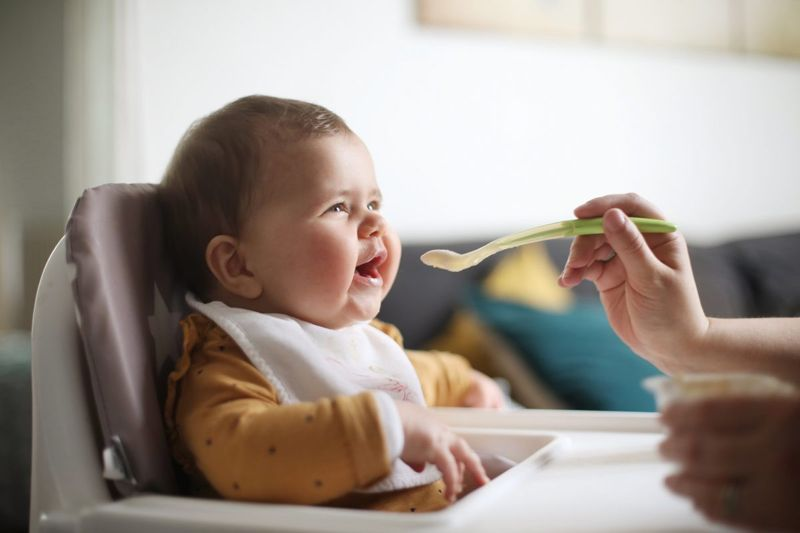 Baby eating at high chair.