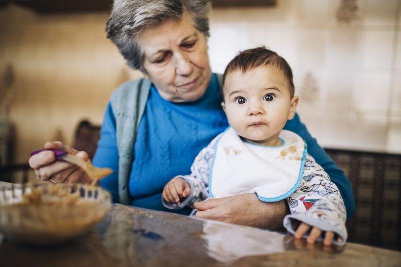 Grandmother feeding grandson.
