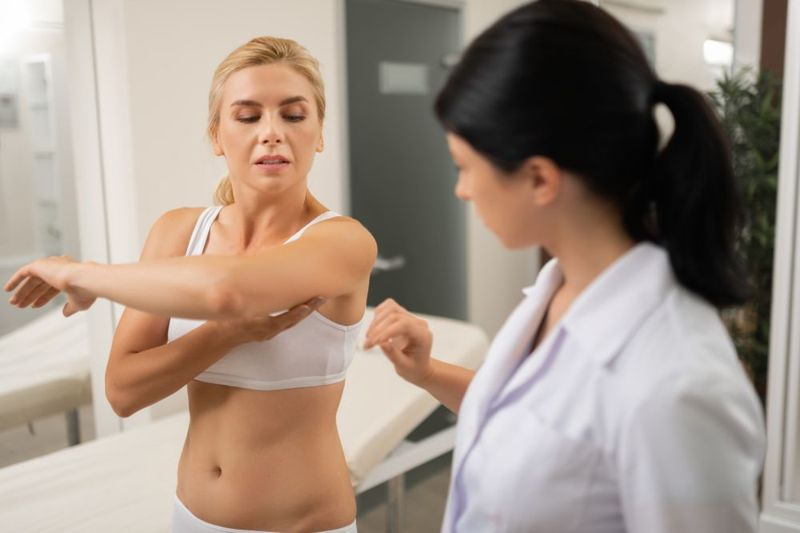 woman showing arm to female doctor