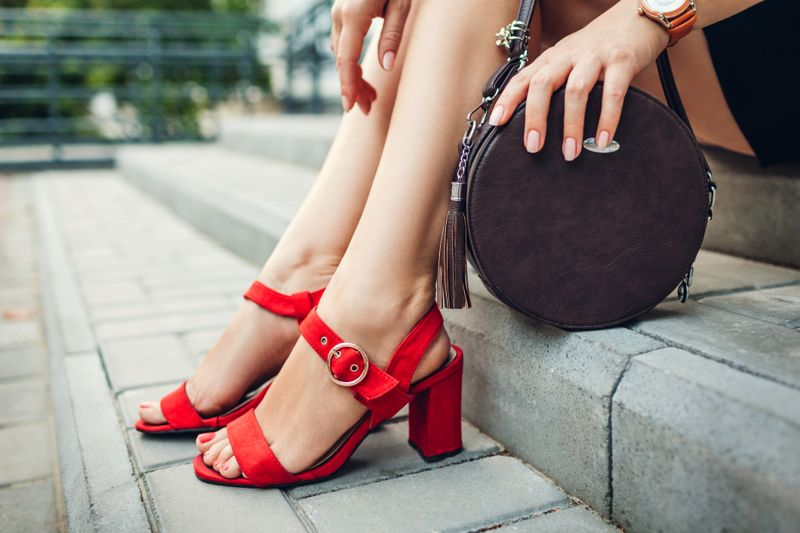Stylish shoes and accessories. Young woman wearing fashionable red high-heeled sandals and holding handbag sitting on stairs outdoors