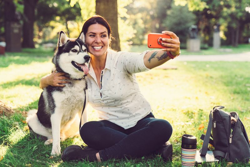 Young woman with her dog taking selfie in the city park
