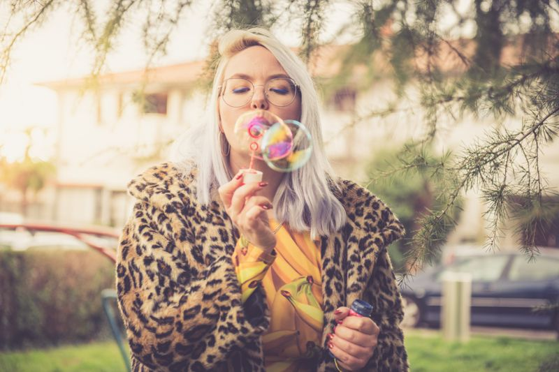 Colorful funky woman blowing soap bubbles