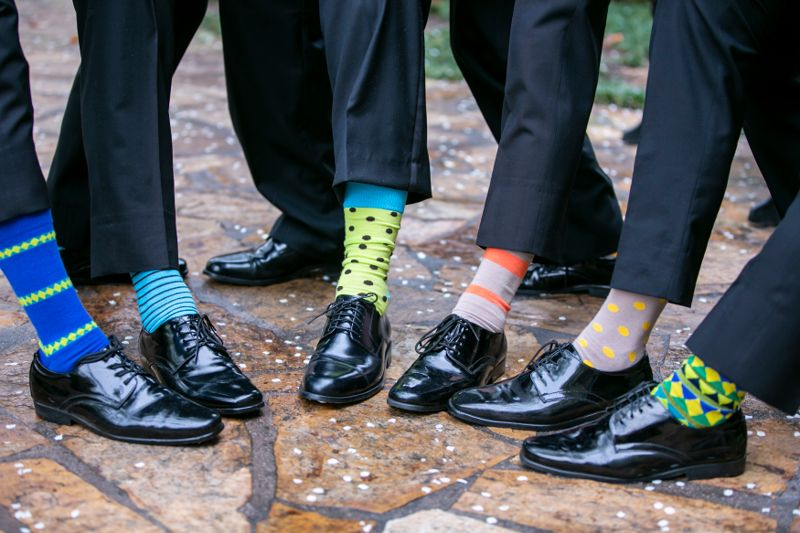 Groomsmen and groom exposing their socks for fun at a wedding reception