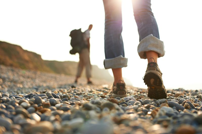 Shot of woman's shoes as a couple walk along a pebble beach towards afternoon sun. Man out of focus in background wearing rucksack.
