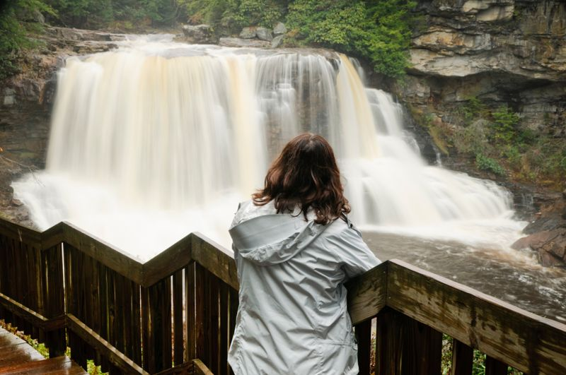 Woman admiring the Blackwater Falls located in the state park by the same name in West Virginia.