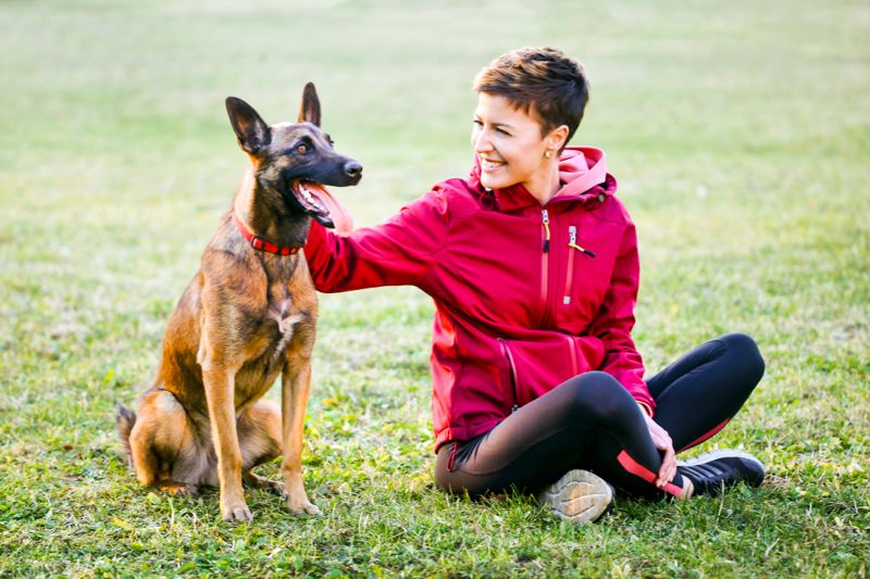 Young beautiful woman enjoying time outdoors with a malinois dog pet. About 20 years old, Caucasian brunette.