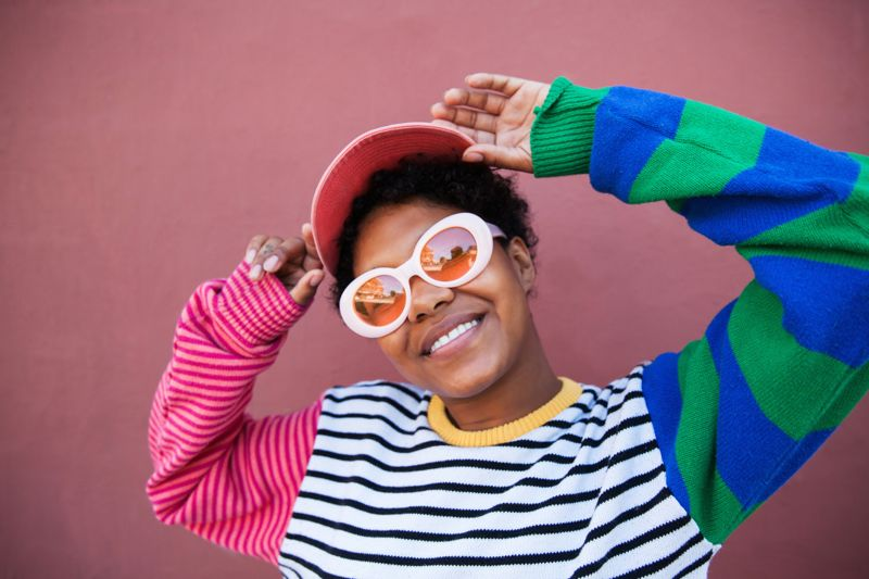 A young woman wearing pink sunglasses and a colorful outfit smiling at the camera
