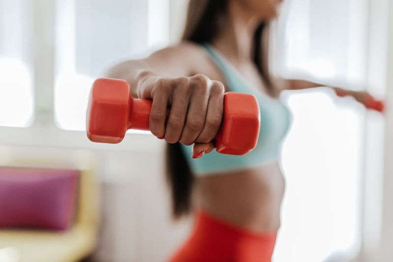 a woman doing lateral raises with dumbbells