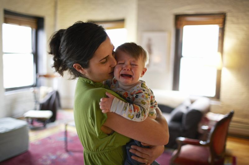 Mother soothing crying baby.