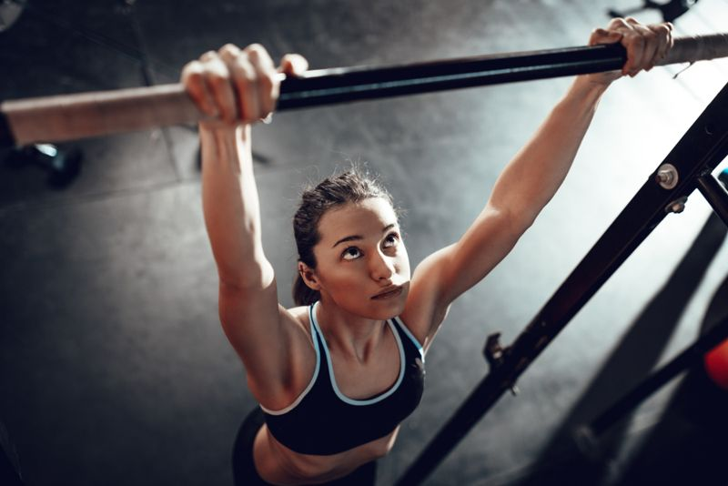 young woman hanging from pull up bar in gym
