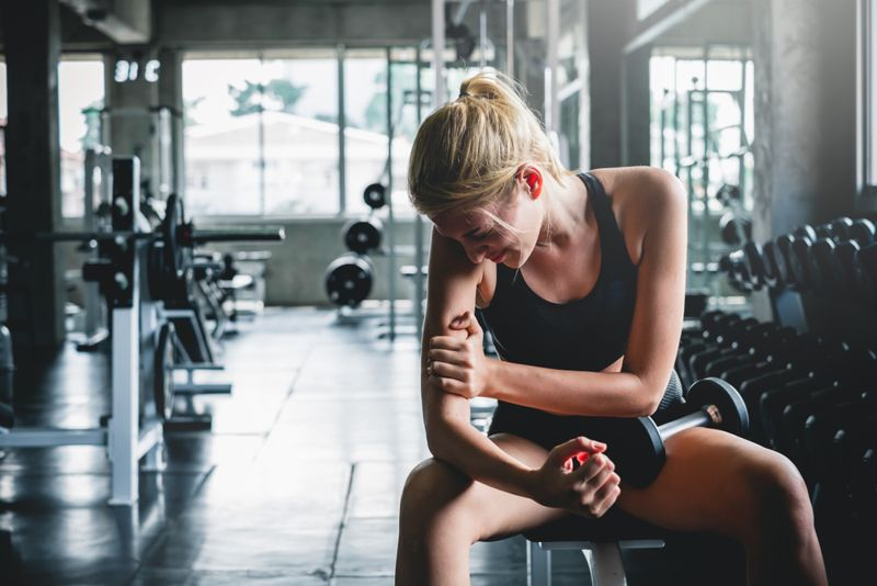 young woman in gym with sore arm