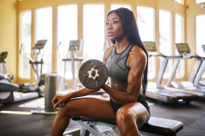 woman in gym lifting a dumbbell, bicep curl