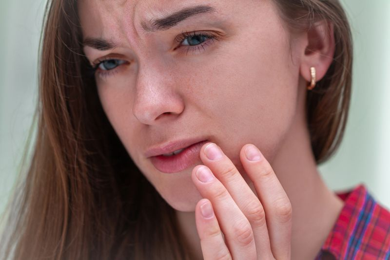young woman touches sore swollen lip