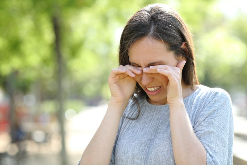 woman rubbing her eyes from outdoor allergies