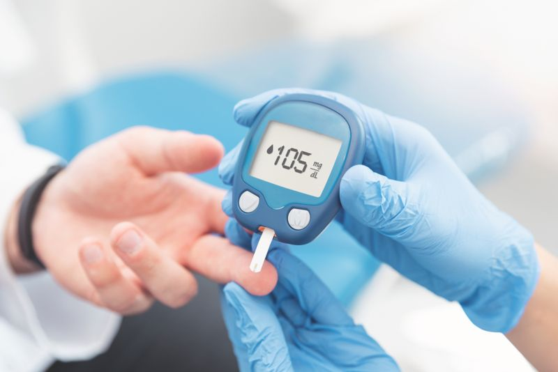 person with diabetes checking insulin on finger