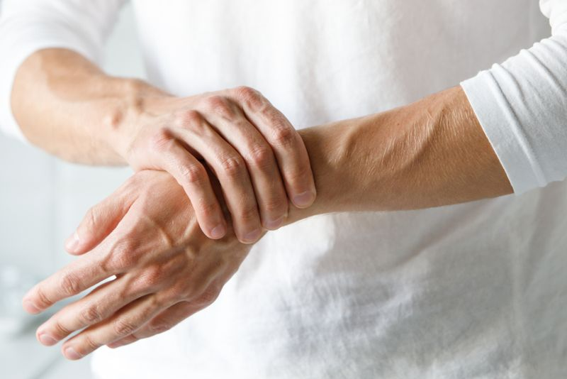 man holding sore wrist arthritis concept