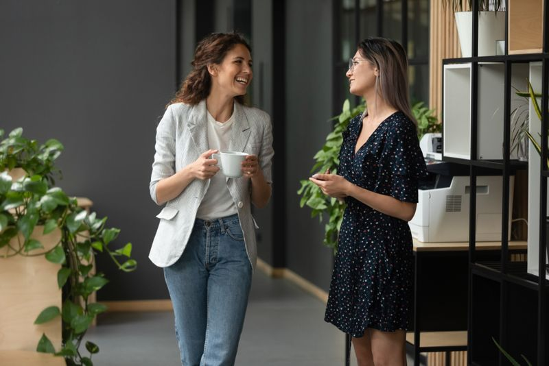 two women at an office talk while having coffee