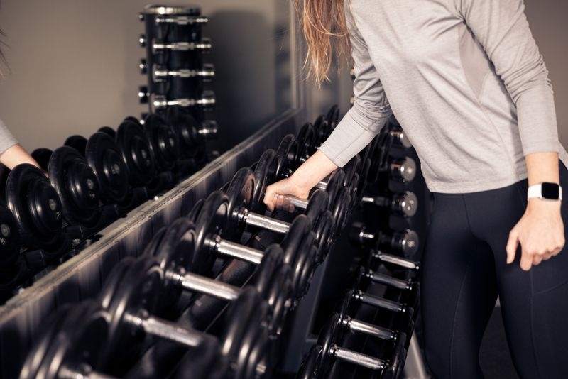 woman choosing a dumbbell from a rack
