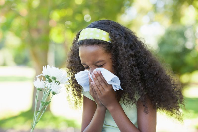 young girl blowing nose pollen allergy