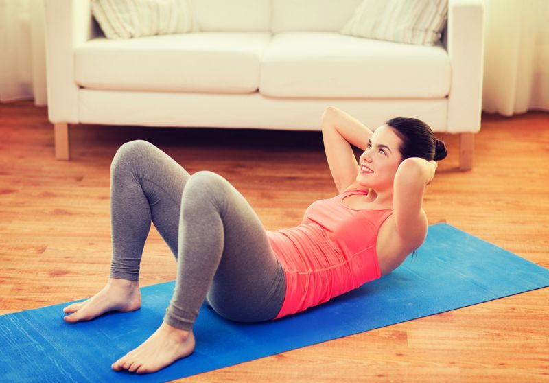 young woman doing crunches exercise on yoga mat