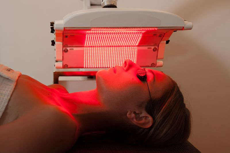 woman under red light therapy panels