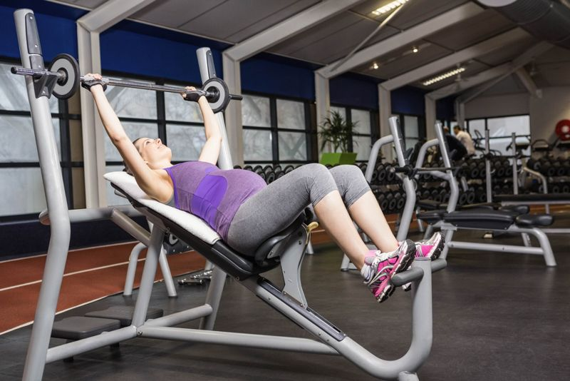 pregnant woman lifting a barbell in a gym